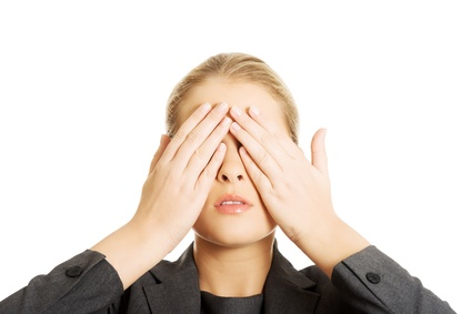 Woman covering her face with both hands